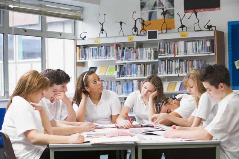 Schulkinder, die in der Schulebibliothek studieren lizenzfreies stockbild