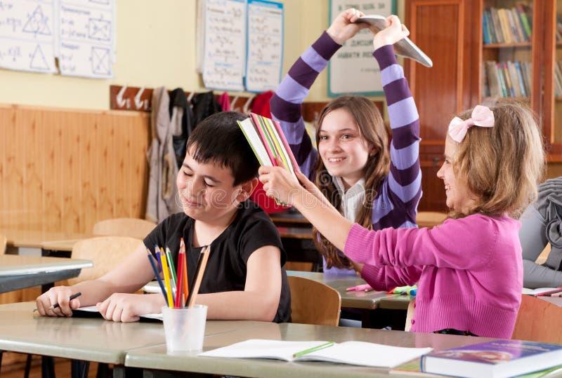 Schulkinder, die mit Büchern kämpfen stockfotografie