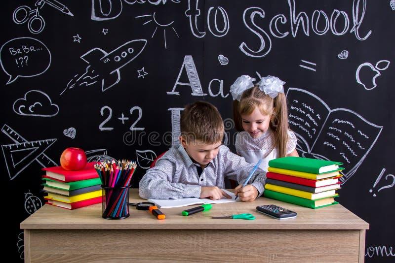 Schulkinder, die am Schreibtisch mit Büchern, Schulbedarf arbeiten Linkshändiger Junge, der den Text und das lächelnde Mädchen be stockfotografie