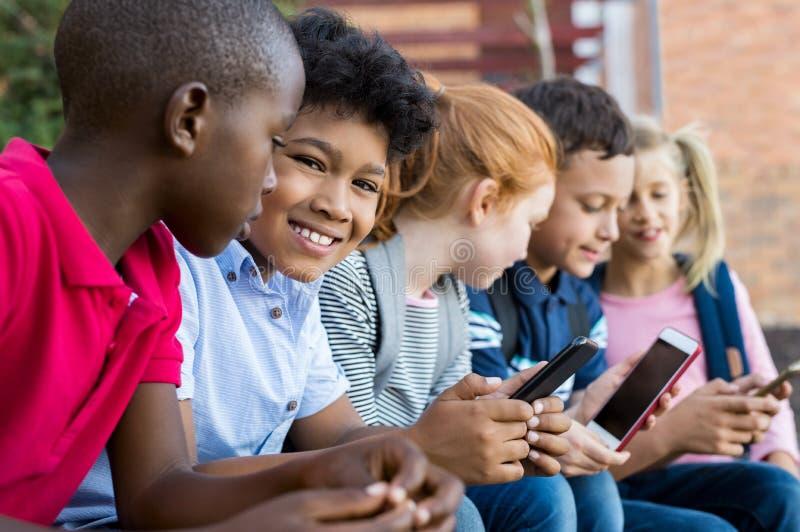 Schulkinder, die Telefone verwenden lizenzfreies stockbild