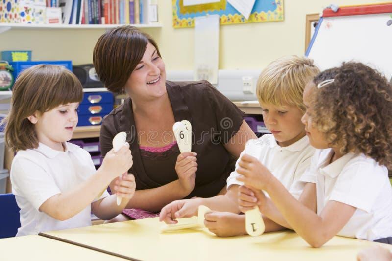 Schulkinder, die Zahlen mit ihrem Lehrer erlernen lizenzfreie stockfotos