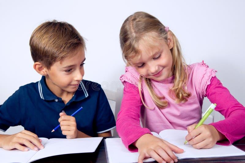 Schulkinder, die zusammen schreiben stockfotos