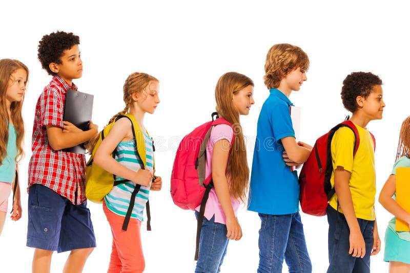 Schulkinder gehen in Übereinstimmung mit Rucksackprofilansicht stockfotos