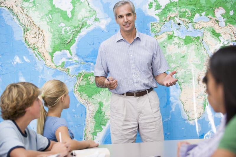 Schulkinder und ihr Lehrer in einer Kategorie stockbild