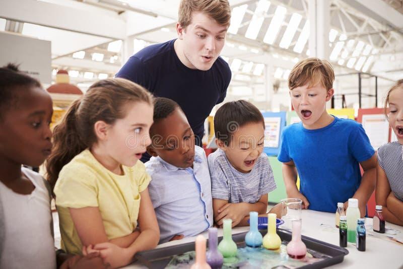 Schulkinder und -lehrer passen Experiment in einer Wissenschaftsmitte auf lizenzfreie stockbilder