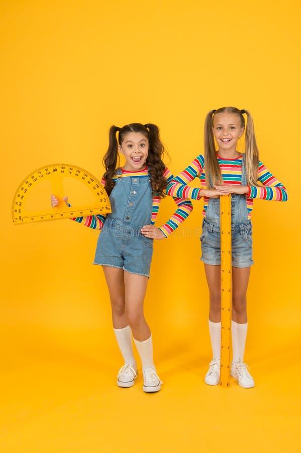 Schulklub Schulkinder mit Messgeräten Kleine Mädchen lernen mit der Geometrie Cute-Schulmädchen lizenzfreie stockfotografie