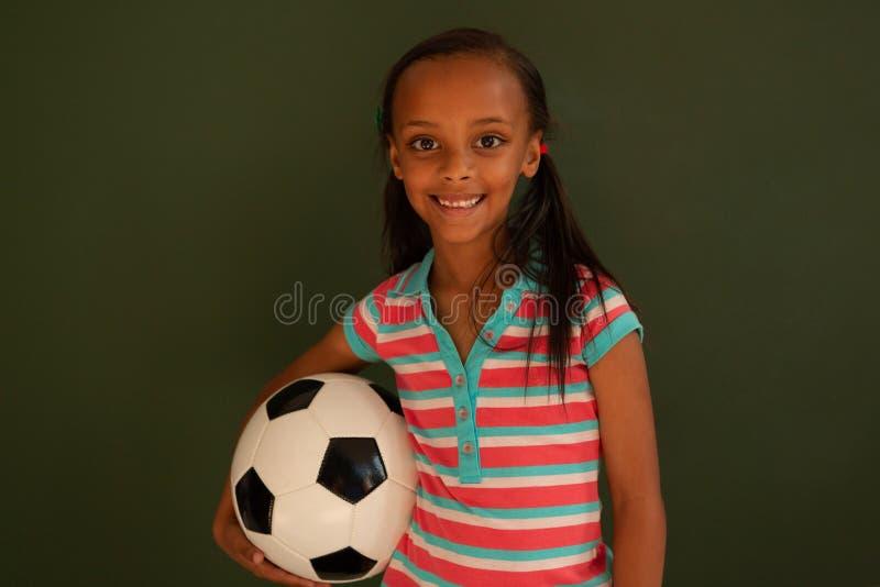Schulmädchenstellung mit Fußball gegen grünes Brett in einem Klassenzimmer lizenzfreie stockfotografie
