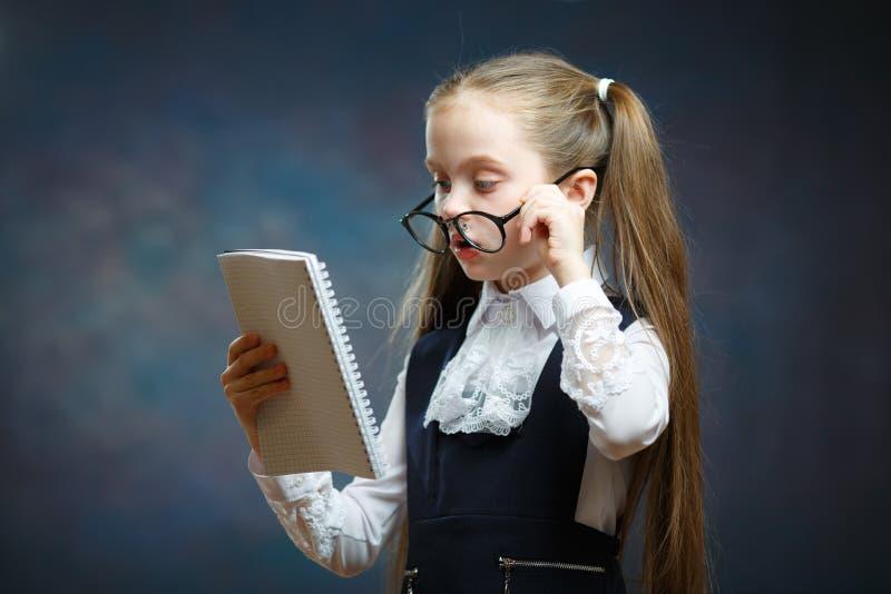 Schulmädchen-Abnutzungs-Glas-einheitlicher Blick auf Notizbuch lizenzfreie stockfotografie