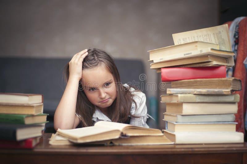 Schulmädchen bereitet sich für die Prüfung mit Büchern vor lizenzfreie stockfotografie