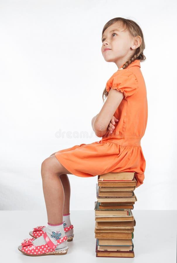 Schulmädchen, das auf Büchern sitzt und oben in der Überraschung schaut lizenzfreies stockbild