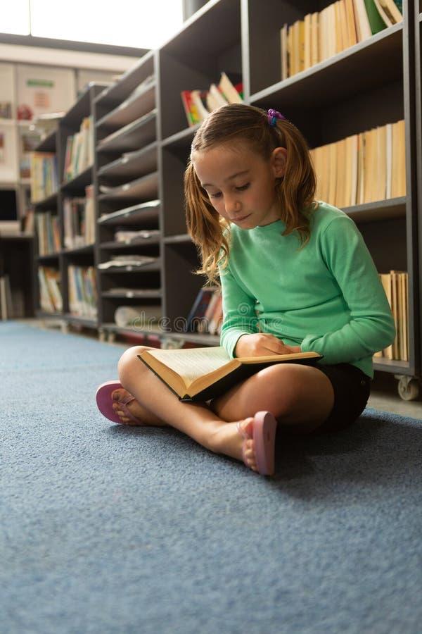Schulmädchen, das auf Boden Position in der im Schneidersitz sitzt und ein Buch in der Bibliothek liest stockfotos