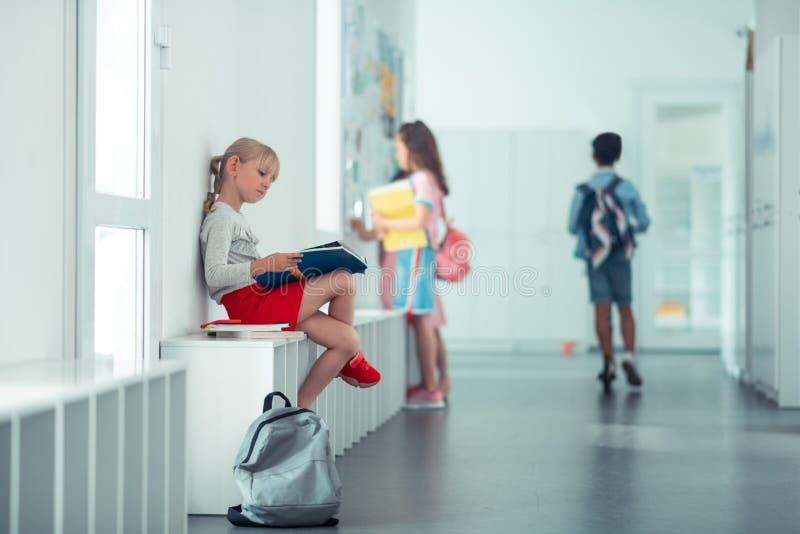 Schulmädchen, das auf dem Fensterbrett sitzt und Informationen wiederholt lizenzfreie stockbilder