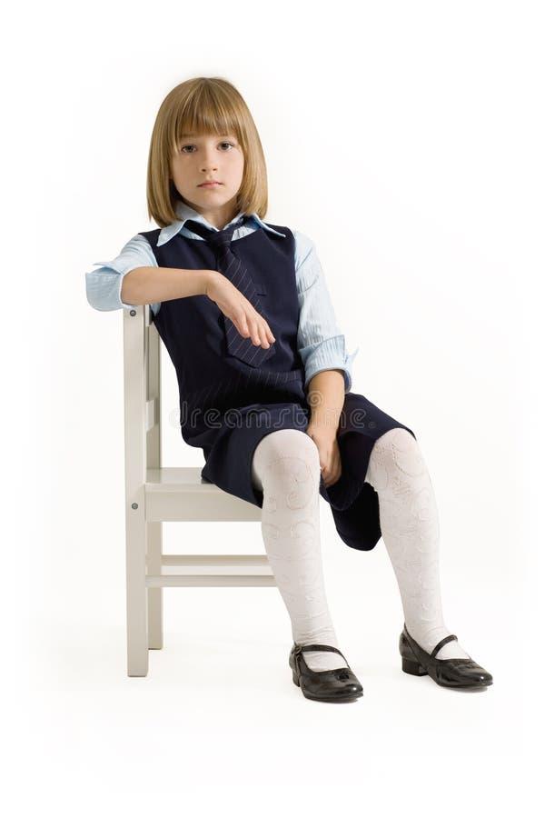 Schulmädchen, das auf dem Stuhl sitzt lizenzfreie stockfotos