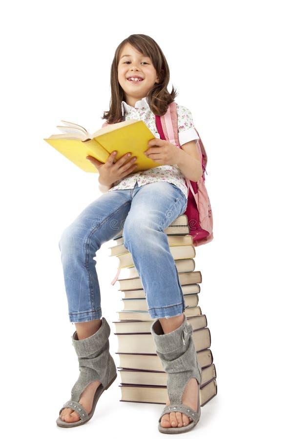 Schulmädchen, das auf den Büchern sitzt stockfoto