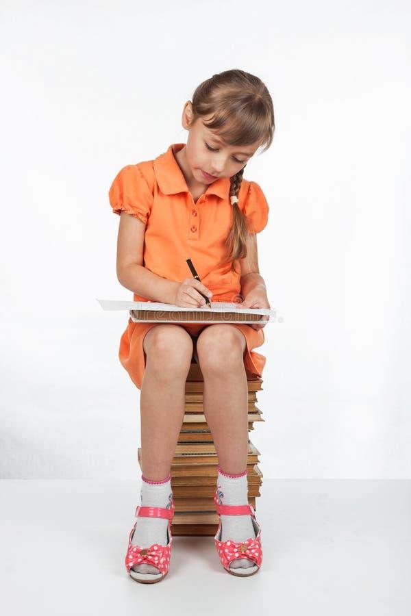 Schulmädchen, das auf den Büchern sitzt und in ein Notizbuch schreibt stockfotografie
