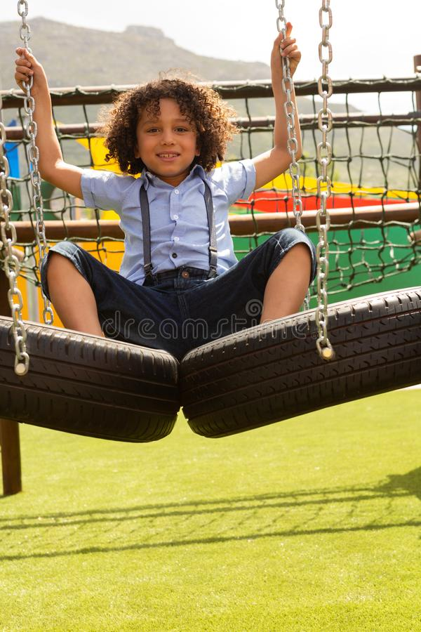 Schulmädchen, das auf hängendem Reifen im Schulspielplatz spielt lizenzfreies stockbild