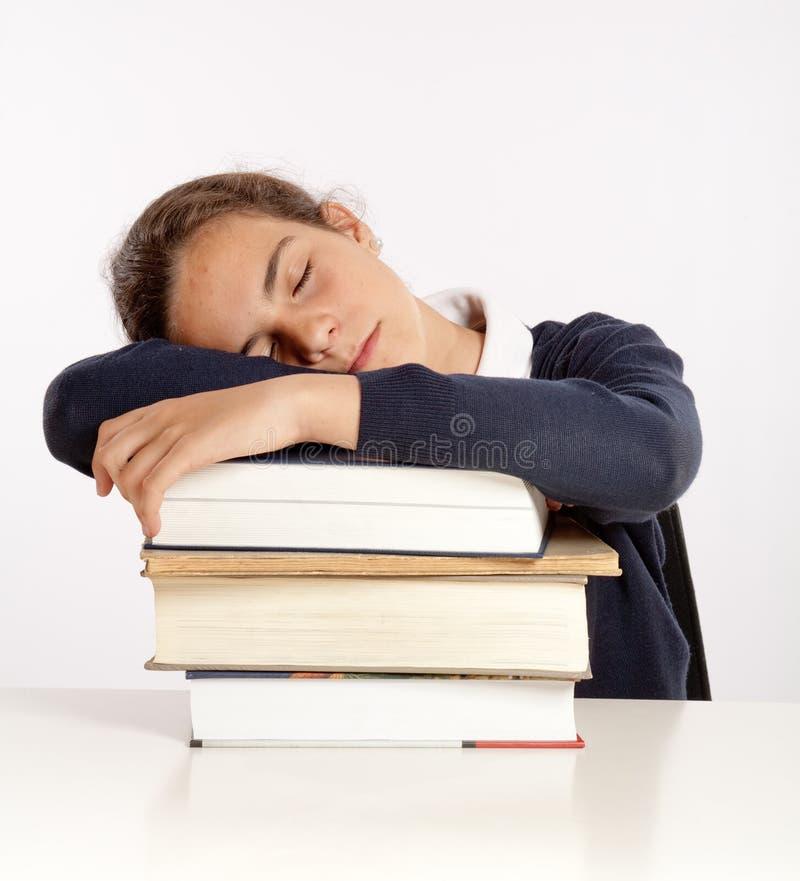 Schulmädchen, das auf ihren Büchern schläft stockbilder