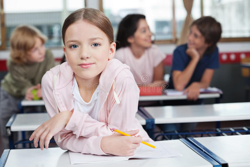 Schulmädchen, das auf Schreibtisch mit Studenten herein sich lehnt lizenzfreie stockfotos