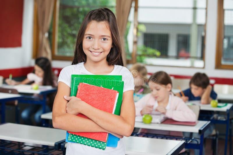 Schulmädchen, das Bücher bei der Stellung am Schreibtisch hält lizenzfreies stockfoto