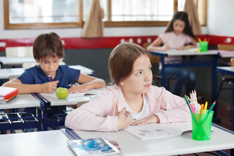 Schulmädchen, das beim Zeichnen in Klassenzimmer weg schaut stockfotografie