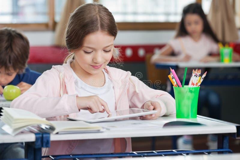 Schulmädchen, das Digital-Tablet im Klassenzimmer verwendet lizenzfreie stockfotos