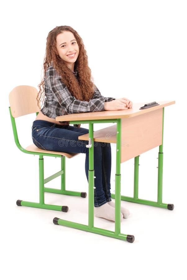 Schulmädchen, das an einem Schreibtisch sitzt lizenzfreie stockfotos
