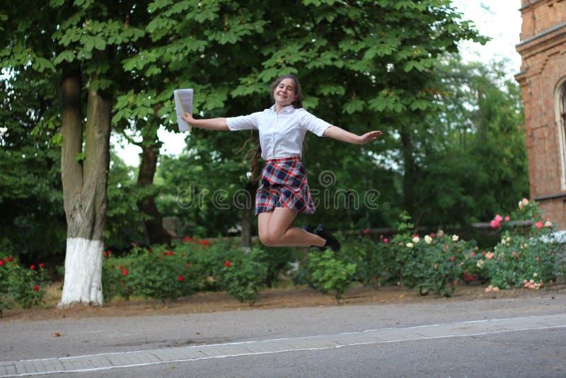 Schulmädchen, das für Freude springt lizenzfreies stockbild