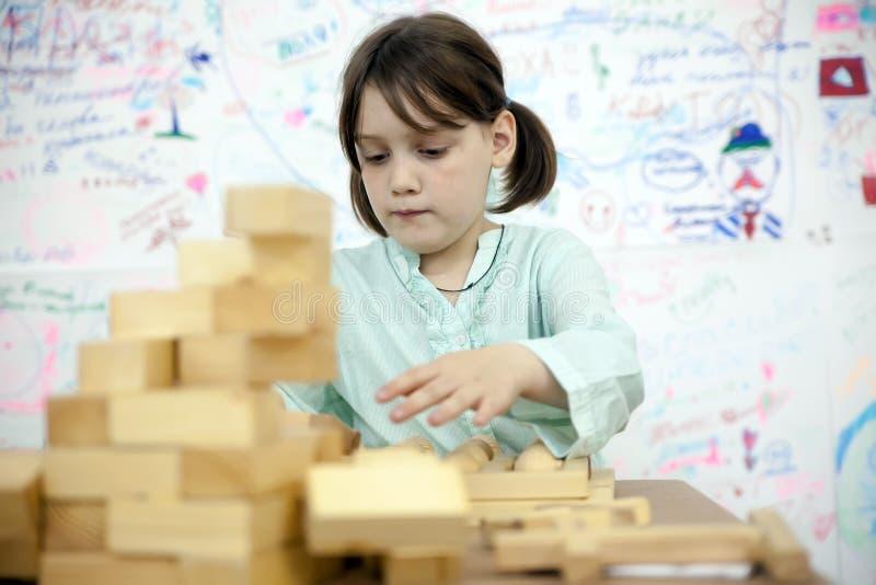 Schulmädchen, das hölzernes Puzzlespiel sammelt stockbilder