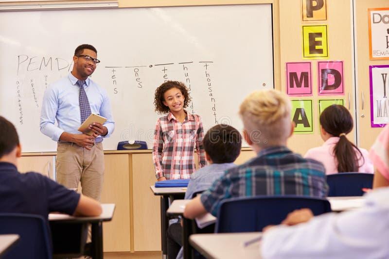 Schulmädchen, das ihren Volksschulemitschülern sich darstellt stockbilder