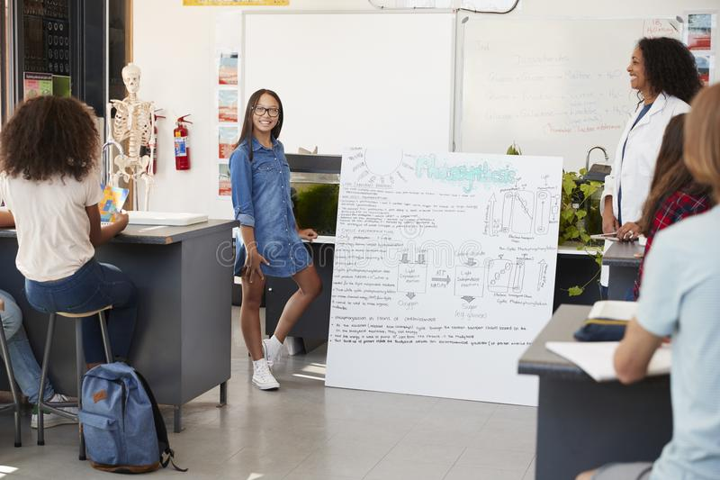 Schulmädchen, das Projekt vor Wissenschaftsklasse darstellt stockbild