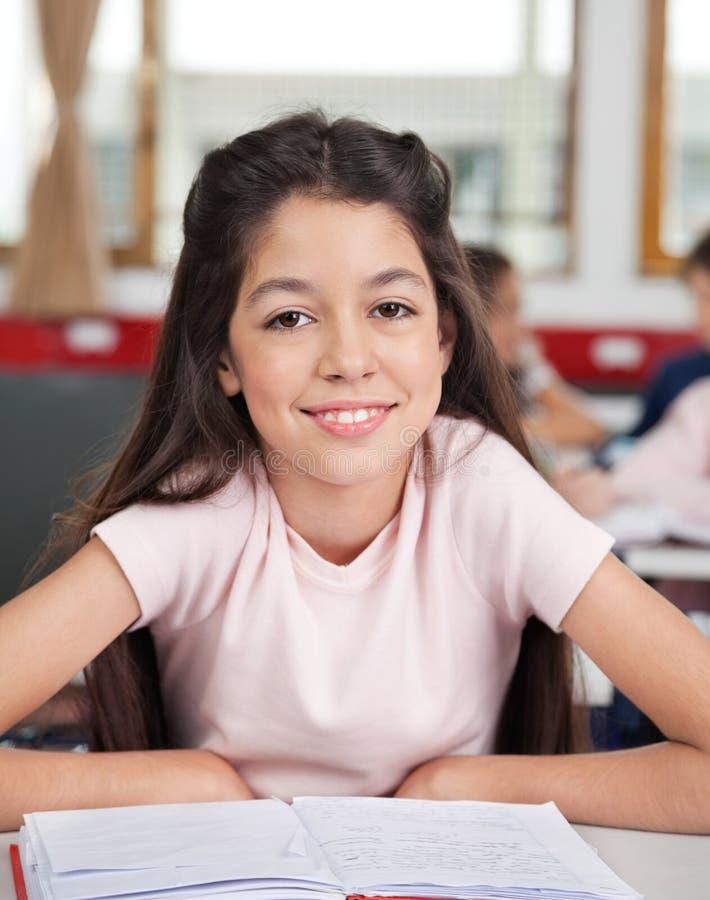 Schulmädchen, das am Schreibtisch im Klassenzimmer sitzt lizenzfreies stockfoto