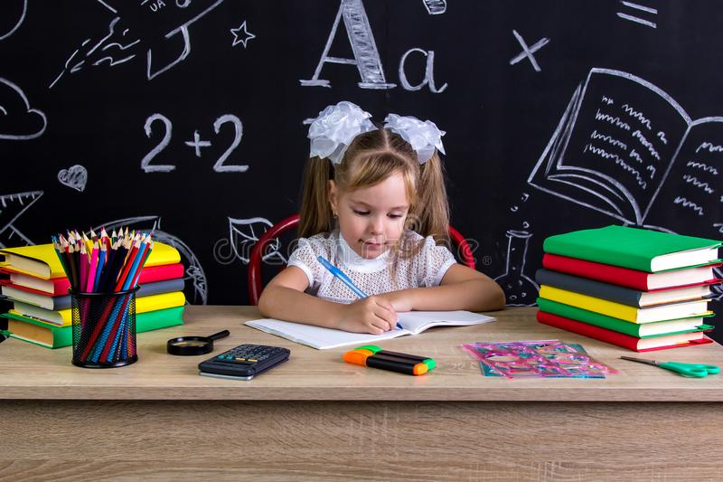 Schulmädchen, das am Schreibtisch mit Büchern, Schulbedarf, schreibend in das Übungsbuch sitzt lizenzfreie stockfotografie