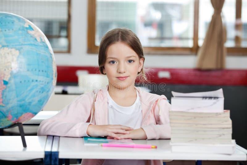 Schulmädchen, das am Schreibtisch sitzt stockfotos