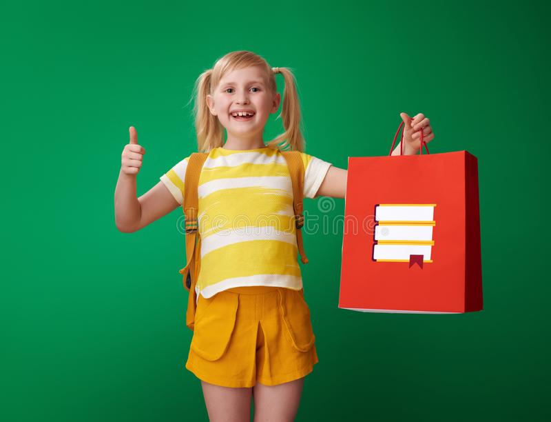 Schulmädchen, das sich Daumen und Einkaufstasche mit Briefpapier zeigt stockbilder