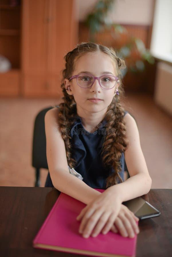 Schulmädchen, das am Tisch mit Lehrbüchern im Klassenzimmer sitzt Mädchen in einem blauen Kleid mit Zöpfen stockbilder