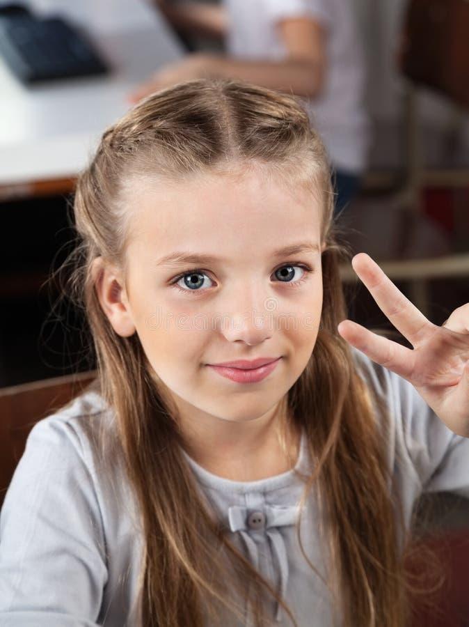 Schulmädchen, das Victory Sign In Computer Lab gestikuliert stockfotos