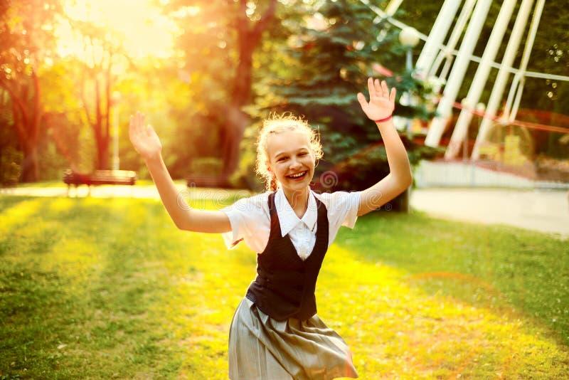 Schulmädchen in der Uniform mit frohem Tanzen der Zöpfe bei Sonnenuntergang I stockbild