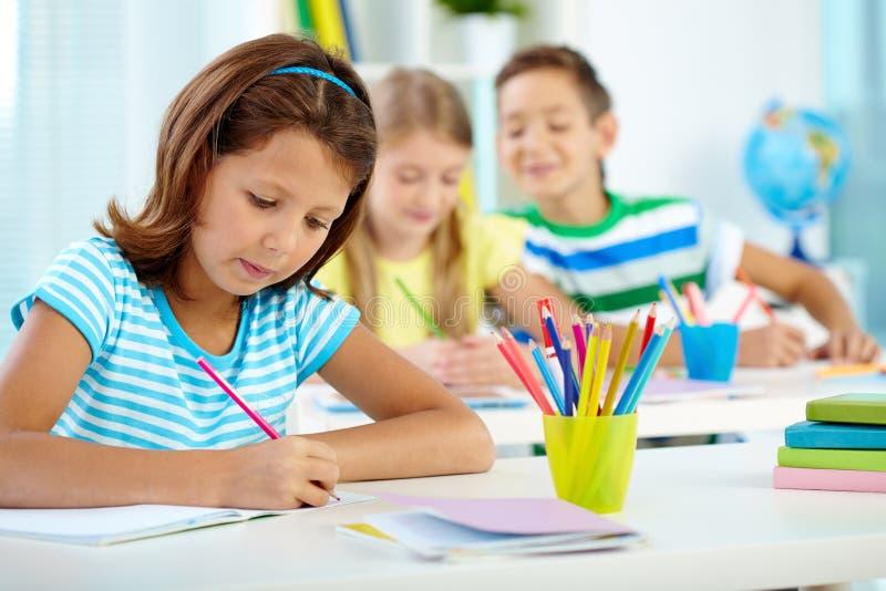 Schulmädchen an der Zeichnungslektion stockfotografie