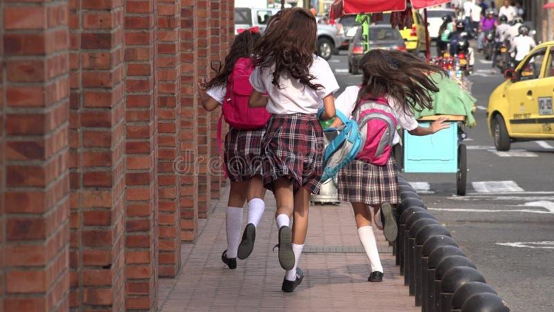 Schulmädchen, die auf Bürgersteig laufen stockfotografie