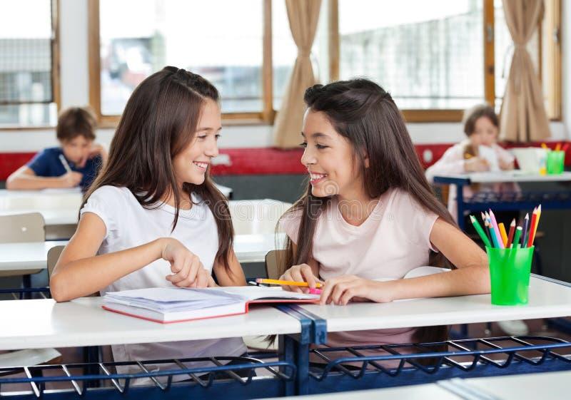 Schulmädchen, die einander im Klassenzimmer betrachten stockfotografie