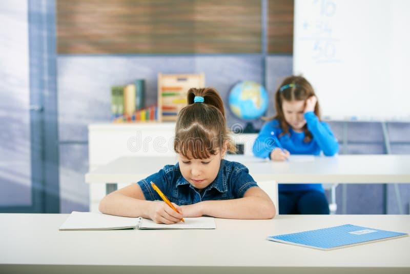 Schulmädchen, die im Klassenzimmer erlernen stockbild