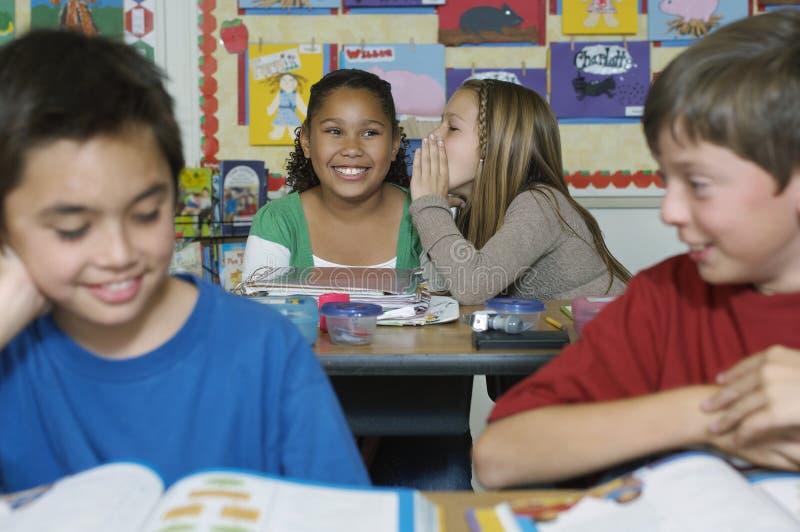 Schulmädchen, die im Klassenzimmer plaudern stockbild