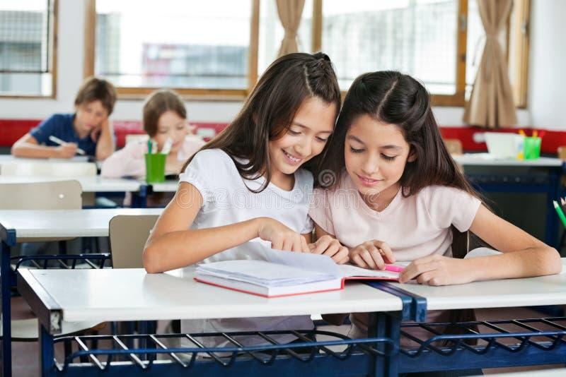 Schulmädchen, die zusammen am Schreibtisch studieren lizenzfreie stockfotos