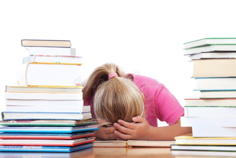 Schulmädchen frustated zwischen vielen Büchern stockfoto