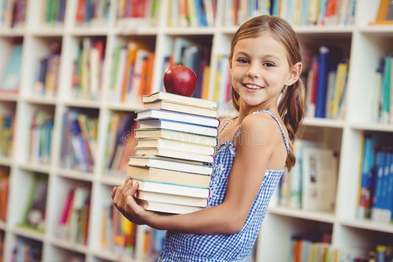 Schulmädchen-Holdingstapel Bücher in der Bibliothek stockbilder