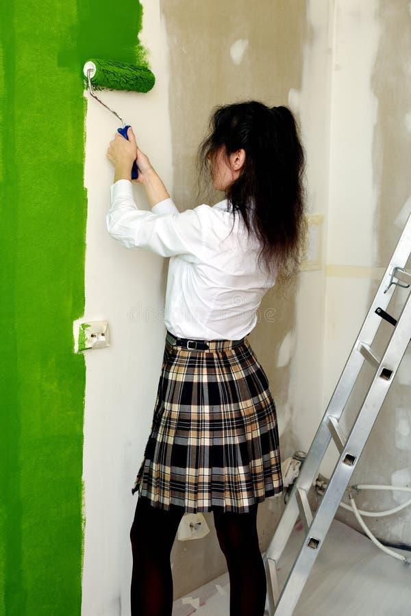 Schulmädchen lernt, wie man eine Wand im Grün mit einer Rolle malt stockfotografie