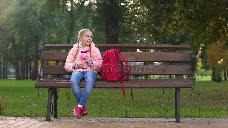 Schulmädchen mit der Thermosflasche, die auf der Bank, stehend nach hartem Tag im Fallpark sitzt still lizenzfreie stockfotografie
