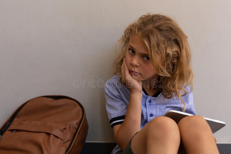 Schulmädchen mit ihrer Schultasche, die auf Boden sitzt und digitale Tablette verwendet lizenzfreie stockfotos