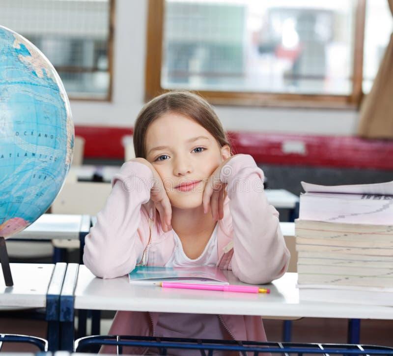 Schulmädchen mit Stapel von Büchern und von Kugel am Schreibtisch stockbilder