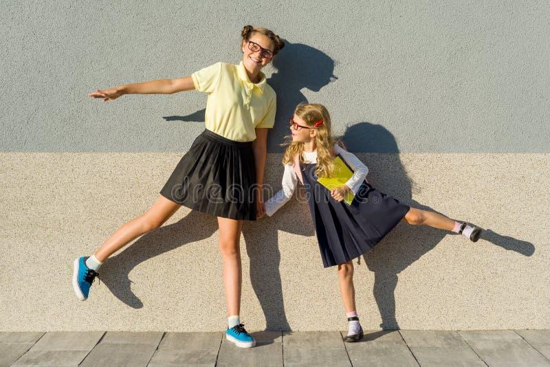 Schulmädchen mit zwei Mädchen grundlegend und Highschool, werfend vor der Kamera, auf dem Weg zur Schule auf lizenzfreie stockfotos
